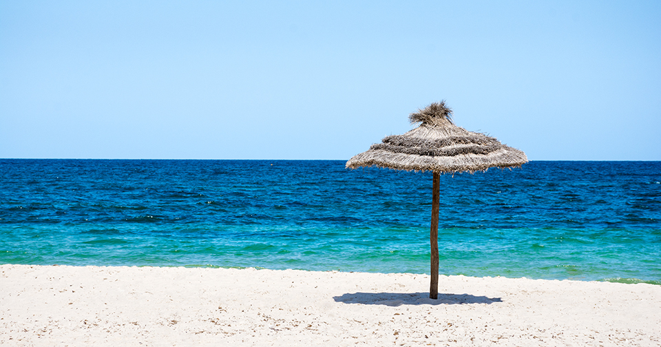 parasol beach on the coast. White sand and blue water of the sea. Panorama.Tunisia